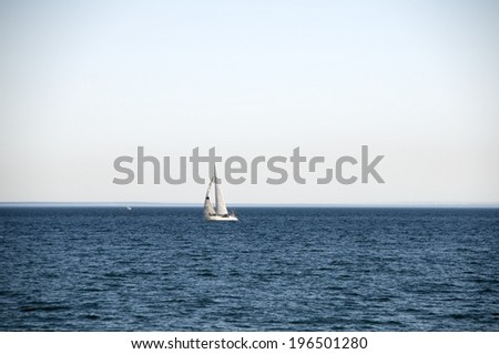 A sailboat alone on the ocean with ripples of waves. - stock photo
