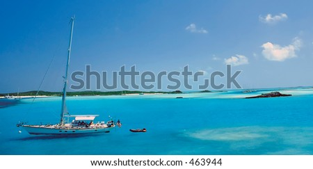 A sailboat is about to make landfall in the beautiful azure and turquoise waters of the Out Islands, Bahamas.