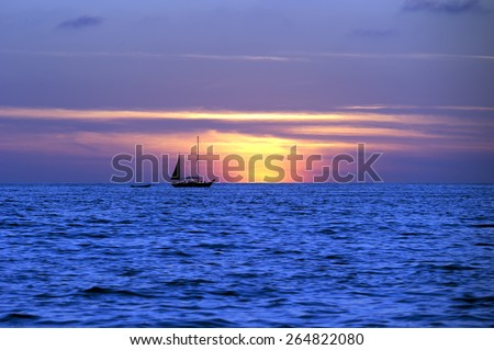 A Sailboat is silhouetted against a vivid sunset sky. - stock photo