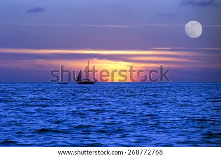 A sailboat moves across the ocean on it's journey lighted by the moon light and the setting sun. - stock photo