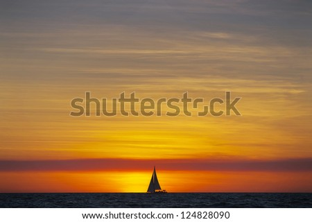 A sailboat on the horizon is silhouetted by the setting sun. - stock photo