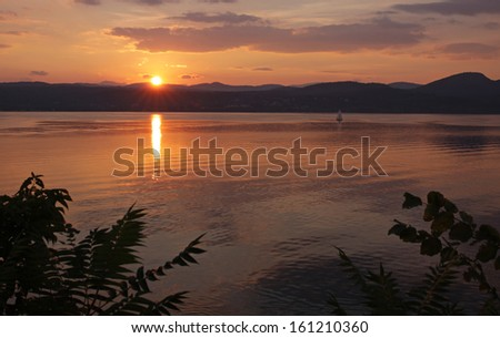 A sailboat sailing on Lake Champlain during a gorgeous sunset.  Shot from the Vermont side near D.A.R. State Park.  - stock photo