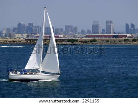 A sailboat speeds along in San Diego Harbor, California - stock photo