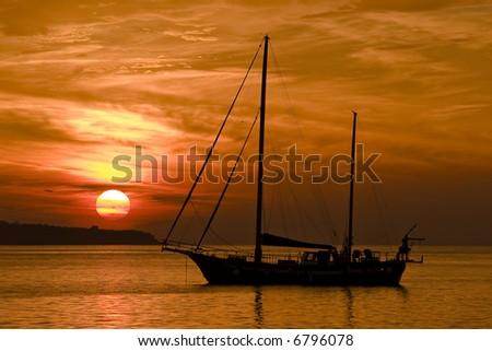 A sailing boat in front of a wonderful Adriatic Sunset in Slovenia - stock photo