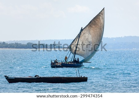 a sailing dhow with full sail running with the wind on a blue ocean heading for harbor - stock photo