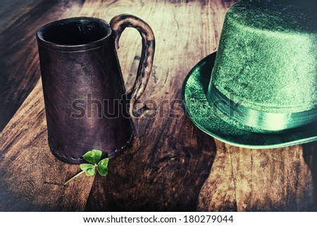 A Saint Patrick's Day background featuring a historic leather mug, green hat, and a shamrock.  Processed for a retro faded look.  - stock photo