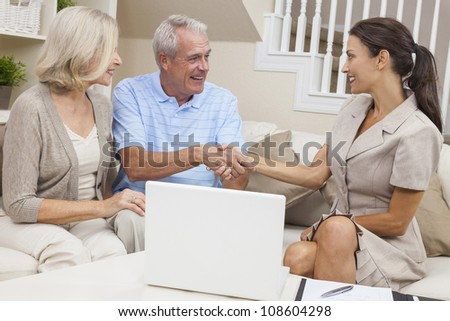 A saleswoman with laptop computer shaking hands with a senior couple at home - stock photo