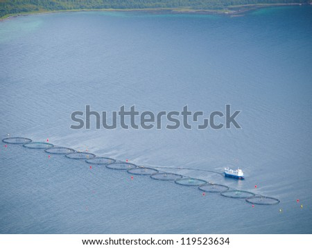 A salmon farm in a fjord in Norway - stock photo