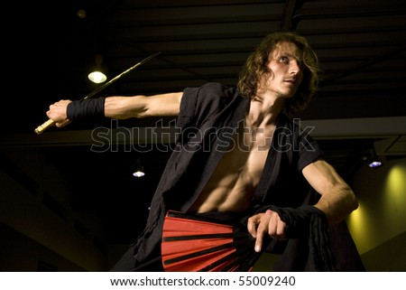 a samurai warrior with a katana/samurai sword and fan poised, alert and ready for action - stock photo