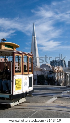 A San Francisco cablecar, with the Transamerica building and Chinatown in the background. - stock photo