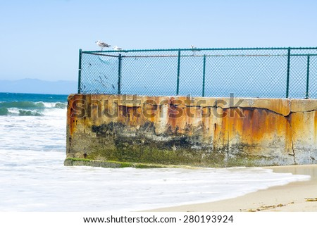 A sand groin used in oceanography to block sand from eroding the beaches, protecting coastal resources from shifting, constant tidal fluctuations.  - stock photo