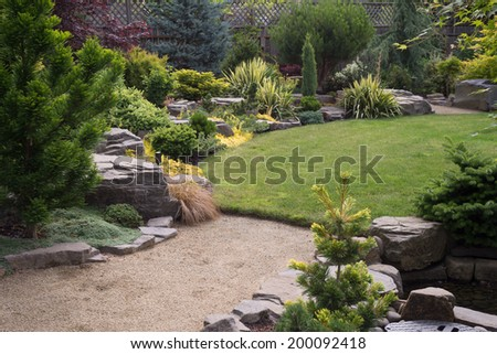 A sand pebbled path leads to a lush green backyard lawn featuring naturally sculptured rocks and a variety of small trees and shrubs - stock photo