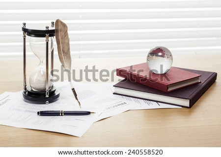 A sand timer(hour glass), feather quill pen, glass globe, graph paper(document) and book on the wooden office desk(table) behind white blind. - stock photo