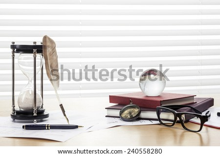 A sand timer(hour glass), feather quill pen, glasses, glass globe, compass, graph paper(document) and book on the wooden office desk(table) behind white blind. - stock photo