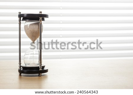 A sand timer(hour glass) on the wooden office desk(table) behind white blind.