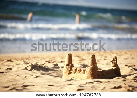 A sandcastle by the ocean - abstract of people  in water - stock photo