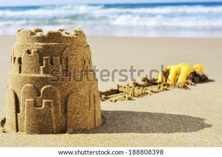 a sandcastle on the sand of a beach - stock photo