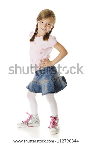 A sassy elementary girl in a denim skirt and sparkling high-top sneakers with bright, heart-covered laces.  On a white background. - stock photo