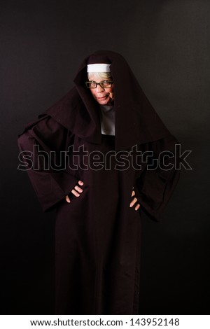 A sassy nun with hands on her hips - stock photo