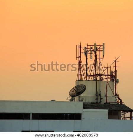 A satellite dish on the building in evening time