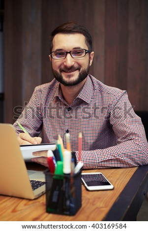 A satisfied young businessman with the glasses using laptop at office and taking notes - stock photo