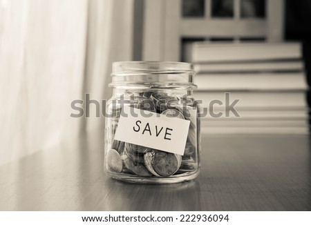 A savings money jar with world coins and save word on label or tag, black and white image - stock photo