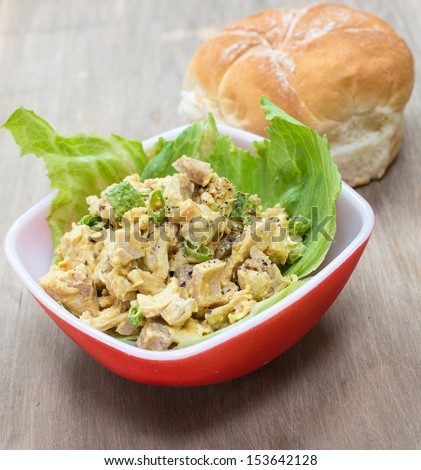 A savory curried chicken salad on lettuce with bun in background. - stock photo