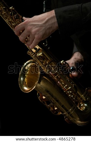 A sax player isolated in black background