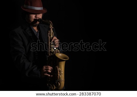 A saxophone player in a dark background - stock photo