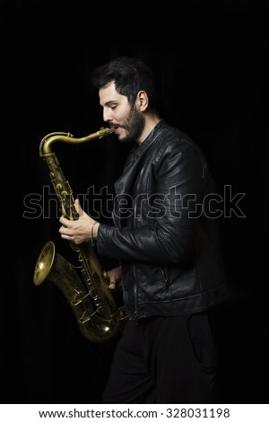 A saxophone player in a dark background. Saxophone Player Saxophonist jazz man with Sax. Leather Jacket dressed saxophone player in a dark club setting