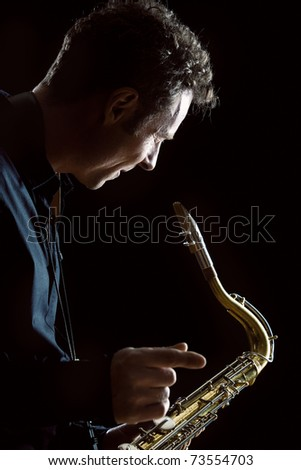 A saxophonist passionately into the musical moment in a dark concert scenario - stock photo