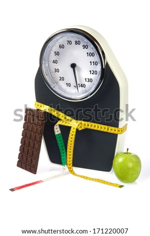 A scale with measuring tape, chocolate and an apple