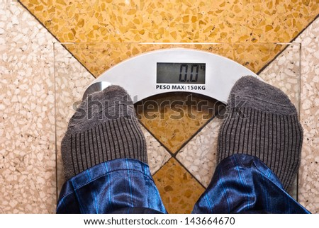 A scale with two feet of the person standing on it - stock photo