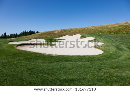 A scalloped edged sand trap with a rake in a golf course with dark green grass next to a hill with a blue sky background. - stock photo
