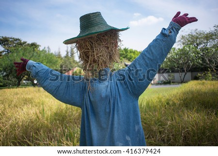 A scarecrow with a head made of straw wearing a blue denim shirt. The scarecrow is standing in the middle of a field with arms outstretched.