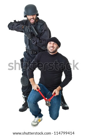 a scared burglar busted by a swat or police officer - stock photo