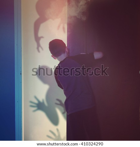 A scared child is looking inside of a closet bedroom at black evil monster ghosts in the background for imagination or ghost concept.
