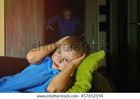 a scared little boy afraid of at night in bed , children's fears of imaginary scary man standing behind him . - stock photo