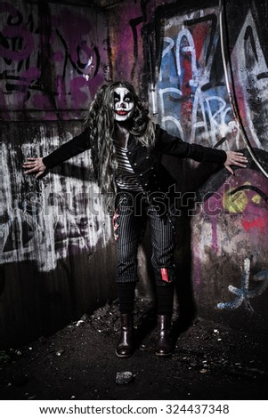 a scary evil clown girl with a wicked makeup - stock photo