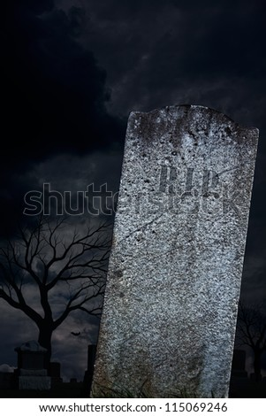 A scary graveyard with a blank grave stone, ready for Halloween.