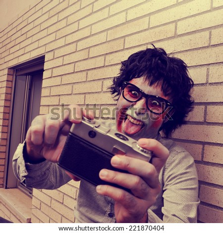 a scary hipster zombie taking a selfie of himself with a vintage camera, with a retro effect - stock photo