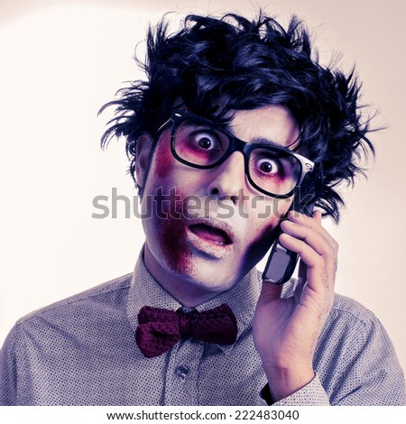 a scary hipster zombie with black plastic-rimmed eyeglasses talking on the phone, with a retro effect - stock photo