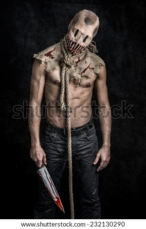 a scary looking scarecrow demon with a bloody knife - stock photo