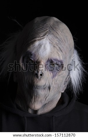A scary portrait of a scary looking zombie on dark background.