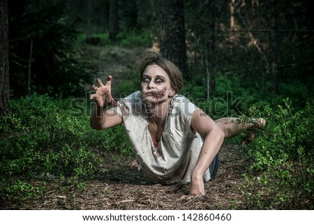 a scary undead zombie girl lying on the ground - stock photo