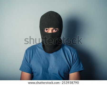 A scary young man is wearing a balaclava - stock photo
