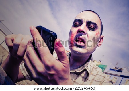 a scary zombie using a smartphone, with a filter effect - stock photo
