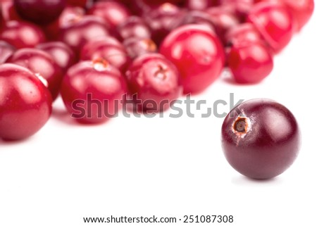 A scattered cranberry and one separate berry