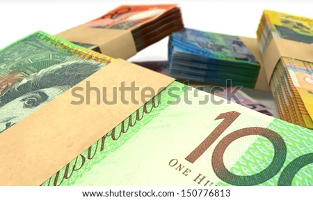 A scattered pile of australian dollar bank notes bundled into value denominations on an isolated background