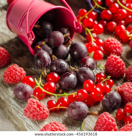 A scattering of fragrant ripe berries. Raspberries, gooseberries and red currants. Seasonal berries. Harvest. Vitamins. Healthy food. The berries are poured from small buckets. Background - old Board. - stock photo